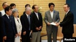 아베 신조 일본 총리(오른쪽 2번재)가 4일 도쿄 총리관저에서 납북 피해자 가족들로부터 청원서를 받고 있다.