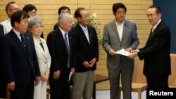 아베 신조 일본 총리(오른쪽에서 2번째)가 지난해 7월 관저에서 납북 피해자 가족들로부터 청원서를 받고 있다.
