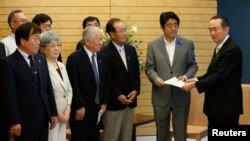 지난 2014년 7월 아베 신조 일본 총리가 도쿄 총리관저에서 납북 피해자 가족들로부터 청원서를 받고 있다. (자료사진)