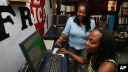 Ciata Victor instructs an unidentified lady inside her Internet cafe in Monrovia, (File photo).
