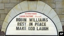 A man takes a photo of a the marquee of the Laugh Factory with a message in memory of actor Robin Williams displayed, in the Hollywood district of Los Angeles Monday, Aug. 11, 2014.