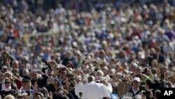 សម្តេចប៉ាប Francis (កណ្តាល) ដោះដូរមួករបស់ព្រះអង្គជាមួយនឹងមួកដែលអ្នកគោរពសាសនាបានថ្វាយព្រះអង្គ នៅខណៈដែលព្រះអង្គមកដល់ទីធ្លារ St. Peter's Square ដើម្បីជួបជាមួយសាធារណៈជន ប្រចាំសប្តាហ៍ ក្នុងទីក្រុងវ៉ាទីកង់ កាលពីថ្ងៃទី២២ ខែមេសា ឆ្នាំ២០១៥។