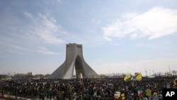 Warga Iran mendengarkan pidato Presiden Hassan Rouhani untuk memperingati ulang tahun revolusi 1979 di Teheran, Iran, Kamis, 11 Februari 2016.