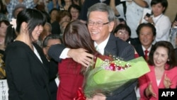 Former Naha Mayor Takeshi Onaga, right, hugs his daughter as they celebrate his victory in the Okinawa gubernatorial election in Naha, the capital of Japan's southern island of Okinawa, Nov. 16, 2014.