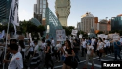 "FILE - Workers from Macau's six major casinos, led by union ""Forefront of Macau Gaming"", march past Casino Lisboa during a demonstration in Macau, Aug. 25, 2014."