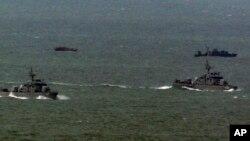지난 2011년 초 한국 해역에 침범했다가 돌아가는 북한 어선(왼쪽 위)과 북한 어선을 호위하기 위해 나온 북한 경비정(오른쪽 위). 아래 쪽은 한국 해군함정들. (자료 사진)