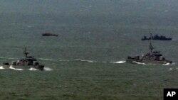지난 2011년 3월 한국 해역에 침범했다가 돌아가는 북한 어선(왼쪽 위)과 북한 어선을 맞기 위해 나온 북한 경비정(오른쪽 위). 아래는 한국 해군함. (자료사진)