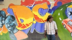 Nigerian-born artist Aniekan Udofia in front of one of his murals