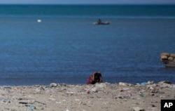 FILE - A woman defecates along the shoreline in Cite Soleil slum, in Port-au-Prince, Haiti, Dec. 25, 2016.