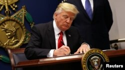 US President Donald Trump signs an executive order to impose tighter vetting of travelers entering the United States, at the Pentagon in Washington, Jan. 27, 2017.