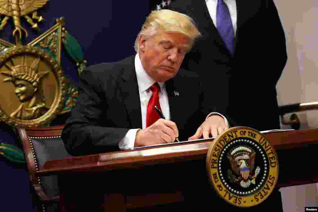El presidente Donald Trump, firma una orden ejecutiva para imponer controles más estrictos a los viajeros que ingresan a Estados Unidos, en el Pentágono en Washington, el 27 de enero de 2017. REUTERS/Carlos Barria - RTSXWMI