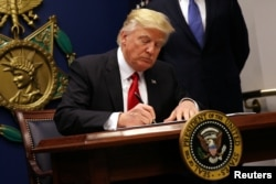 FILE - U.S. President Donald Trump signs an executive order to impose tighter vetting of travelers entering the United States, at the Pentagon in Washington, Jan. 27, 2017.