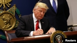 FILE - President Donald Trump signs an executive order to impose tighter vetting of travelers entering the United States, at the Pentagon in Washington, Jan. 27, 2017.