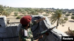 A Libyan rebel fighter points out positions of forces loyal to leader Moammar Gadhafi at Misrata's western front line, some 25 kilometres from the city center May 26, 2011