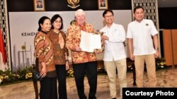 CEO Freeport-McMoran Richard Adkerson (tengah) dan Direktur Utama PT Inalum Budi G Sadikin menunjukkan dokumen usai penandatanganan Sales Puchase Agreement di Jakarta, Kamis sore (27/9). (Foto: courtesy)