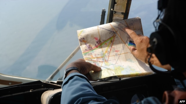 A Vietnamese Air Force crew member checks a map while searching for the missing Malaysia Airlines flight off Vietnam's island Phu Quoc on March 11, 2014.
