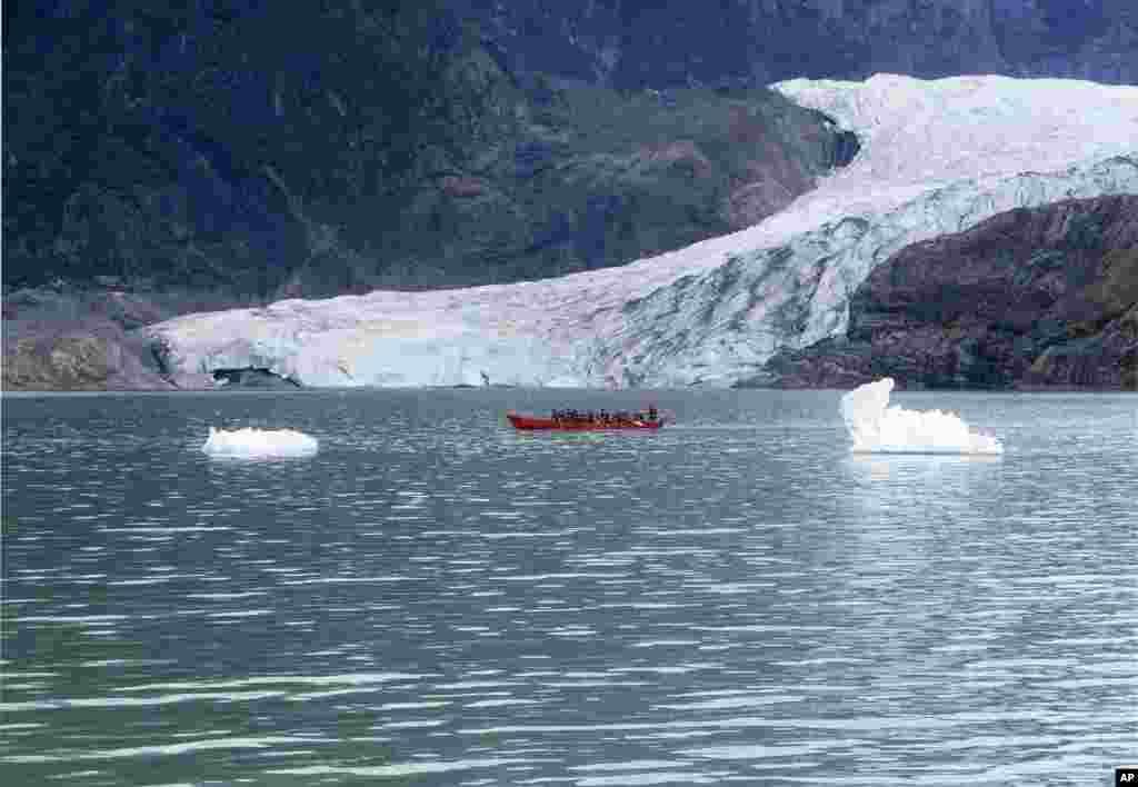 کایاک سواران در مقابل کوه یخ مِندِنهال در ایالت آلاسکای آمریکا. این کوه یخ به غارهای یخی زیبایش شهرات دارد.