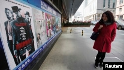 "A woman looks at a poster of the film ""Django Unchained"" outside a cinema in Beijing, April 11, 2013."