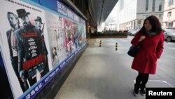 4月11日﹐一名女子在北京街頭觀看電影'決殺令'的廣告