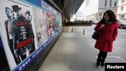 """Seorang perempuan China mengamati poster film """"Django Unchained"""" di luar bioskop di Beijing (11/4)."""
