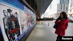 """Seorang warga mengamati poster film """"Django Unchained"""" di luar sebuah gedung bioskop di Beijing, 11 April 2013 (Foto: dok). Film garapan Quentin Tarantino ini ditarik dari peredaran pada hari pemutaran perdananya di China, Kamis (11/4) ."""