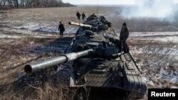 Phiến quân ly khai của quân đội tự xưng Cộng hòa Nhân dân Donetsk đứng trên nóc xe tăng tại một chốt kiểm soát trên đường từ thị trấn Vuhlehirsk đến Debaltseve, 18/2/2015.