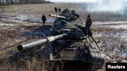 Pro-Russian rebels stand on top of their tank at a checkpoint on a road connecting the towns of Vuhlehirsk and Debaltseve, Donetsk region, eastern Ukraine, Feb.18, 2015.