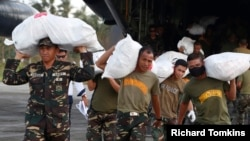 Soldiers carry sacks containing relief goods for typhoon victims in Borongan, Eastern Samar, in central Philippines, Dec. 10, 2014.