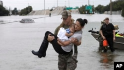 Houston Police SWAT officer Daryl Hudeck carries Catherine Pham and her 13-month-old son Aiden after rescuing them from their home surrounded by floodwaters from Tropical Storm Harvey Sunday, Aug. 27, 2017, in Houston.