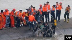 "A 65-year-old woman, center, is rescued by divers from the Dongfangzhixing or ""Eastern Star"" vessel which sank in the Yangtze river in Jianli, central China's Hubei province, June 2, 2015. (AFP Photo)"