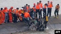 Seorang perempuan berusia 65 tahun (tengah), diselamatkan oleh para penyelam dari kapal Dongfangzhixing (Eastern Star) yang tenggelam di sungai Yangtze di Jianli, propinsi Hubei, China tengah (2/6).