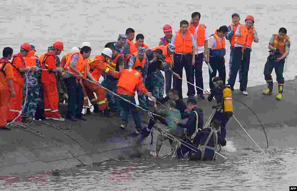 "A 65-year-old woman is rescued by divers from the Dongfangzhixing or ""Eastern Star"" vessel which sank in the Yangtze river in Jianli, central China's Hubei province, June 2, 2015."