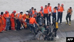 "A 65-year-old woman, center, is rescued by divers from the Dongfangzhixing or ""Eastern Star"" vessel which sank in the Yangtze river in Jianli, central China's Hubei province, June 2, 2015."