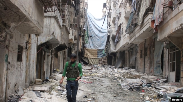 FILE photo: A Free Syrian Army fighter carries handcuffs as he walks along the rubble of damaged buildings in Aleppo's Salaheddine neighborhood, Nov. 7, 2013.