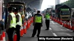 Petugas polisi mengenakan masker berjaga di pos pemeriksaan jalan raya di Bekasi, menyusul larangan mudik lebaran untuk mencegah penyebaran virus corona (COVID-19), 24 April 2020. (Foto: Willy Kurniawan/Reuters/dok)