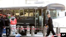 Police officers investigate the crime scene after a gunman fired shots at US soldiers on the bus outside Frankfurt airport, Germany, killing two airmen and wounding two before being taken into custody, March 2, 2011