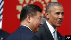FILE - China's President Xi Jinping, left, and then-U.S. president Barack Obama are seen at a summit in Lima, Peru, Nov. 20, 2016. Xi reportely hosted Obama Thursday in Beijing.
