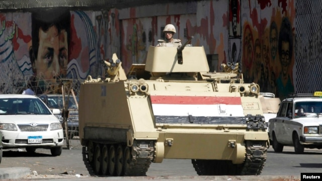 A soldier stands guard in a tank in Tahrir Square in Cairo, Aug. 14, 2014.