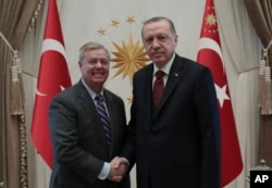 Turkey's President Recep Tayyip Erdogan, right, and U.S. Republican Senator Lindsey Graham shake hands before a meeting in Ankara, Turkey, Jan. 18, 2019.