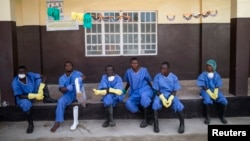 Health workers rest outside a quarantine zone at a Red Cross facility in the town of Koidu, Kono district, eastern Sierra Leone, Dec. 19, 2014.