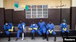 Le personnel de santé assis devant une maison dans une zone de quarantaine dnas les instatallations de la Croix Rouge au village de Koidu, district de Kono, dans l'est de la Sierra Leone, le 19 décembre 2014.