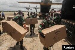 Para anggota TNI membantu distribusi peralatan medis ke sejumlah rumah sakit di tengah wabah virus corona, di Bandara Tjilik Riwut, Kalimantan Tengah, 4 April 2020. (Foto: Antara via Reuters)