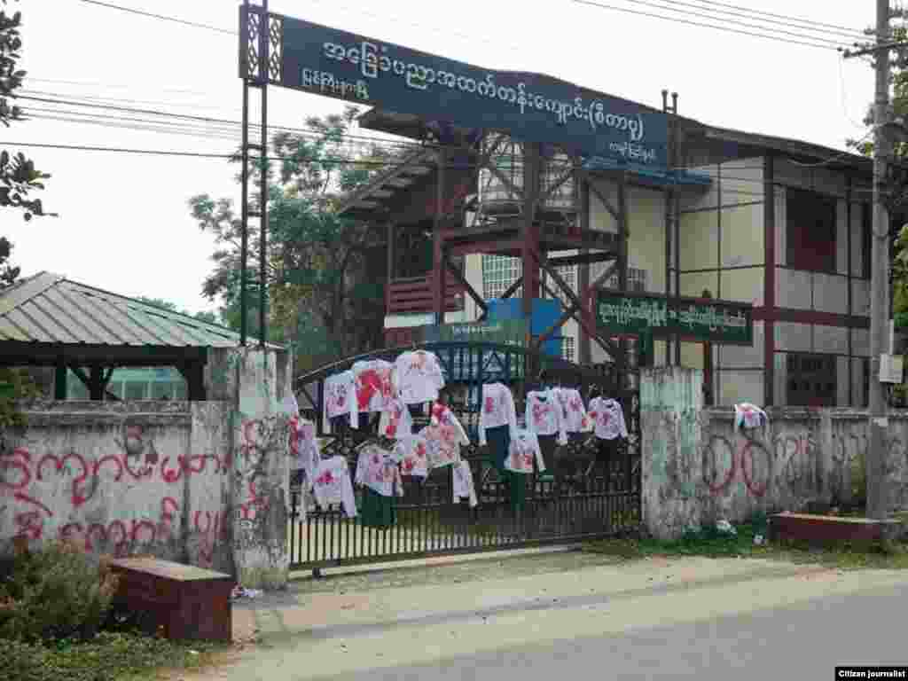 School uniforms with red stains to represent bloody crackdowns by Myanmar security forces during anti-coup protest are displayed on the gate of a high school in Myitkyinar, the capital of Kachin State.