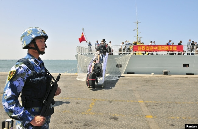 FILE - A navy soldier in the People's Liberation Army stands guard as Chinese citizens board the naval ship 'Linyi' at a port in Aden.