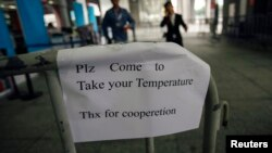 A sign requesting people to come have their temperature taken is seen at the entrance to the Canton Fair in Guangzhou, Guangdong province.