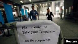 Một bảng yêu cầu người dân đến đo nhiệt độ tại lối vào hội chợ Canton ở Quảng Châu, tỉnh Quảng Đông, Trung Quốc.