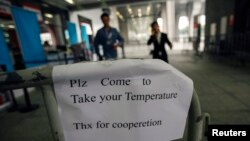 A sign requesting people to come have their temperature taken is seen at the entrance to the Canton Fair in Guangzhou, Guangdong province, Oct. 26, 2014.