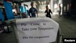 Tấm bảng tại lối ra vào Hội chợ Canton ở Quảng Châu, tỉnh Quảng Đông, Trung Quốc hôm 26 tháng 10, 2014 yêu cầu khách vào hội chợ đến đo thân nhiệt.