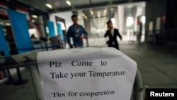 广交会入口处的告示要求人们测量体温(2014年10月26日)