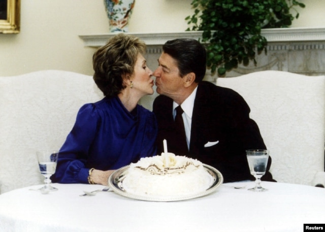 President Ronald Reagan and his wife Nancy kiss on their wedding anniversary in the White House March 4 1985.